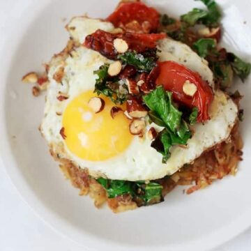 Breakfast potato latkes topped with egg, kale, tomatoes and Tamari almonds