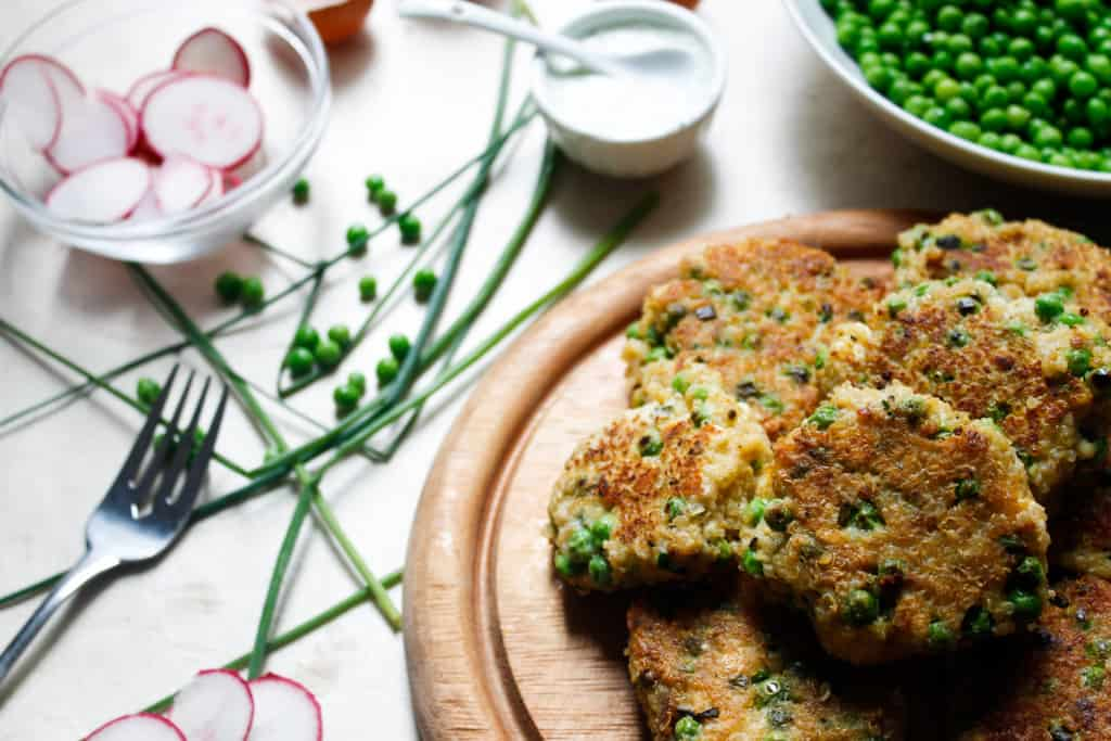 Quinoa fritters with peas, feta and yogurt-herb sauce are everything that will make you fall in love with this gluten-free, energy-filled seed. Make them bigger for great veggie burger patties! #glutenfree and #vegetarian