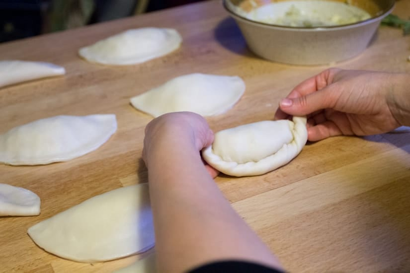 hands rolling empanadas