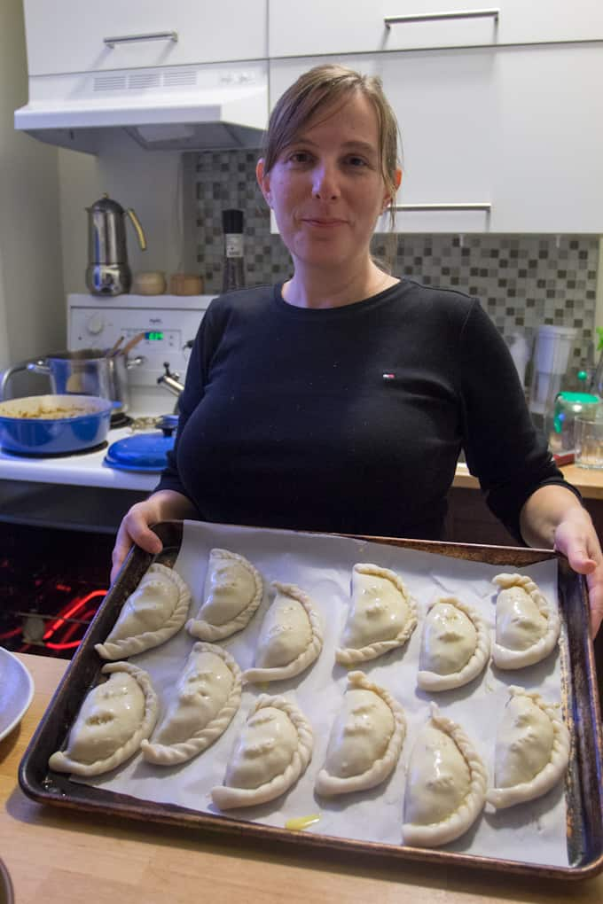 Girl with baking sheet of empanadas