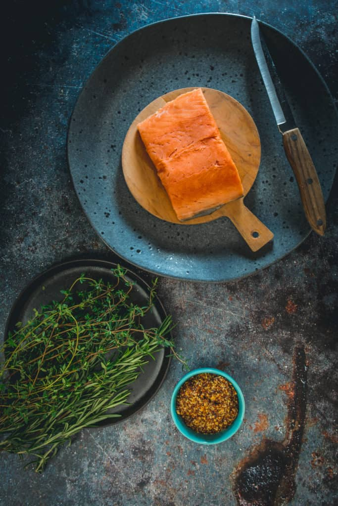 ingredients on plates: Sockeye salmon, herbs and mustard