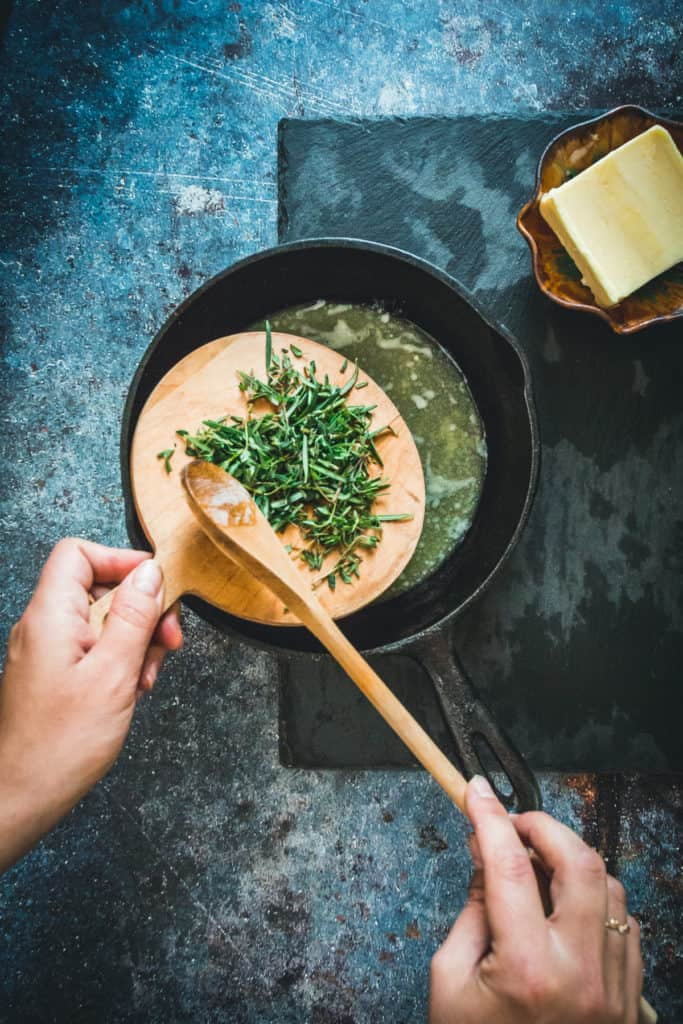 Adding chopped herbs to melted butter in cast-iron pan