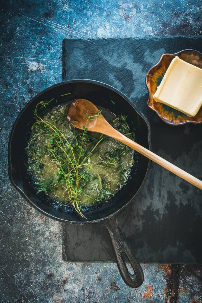 Herbs in melted butter cooking in cast iron pan