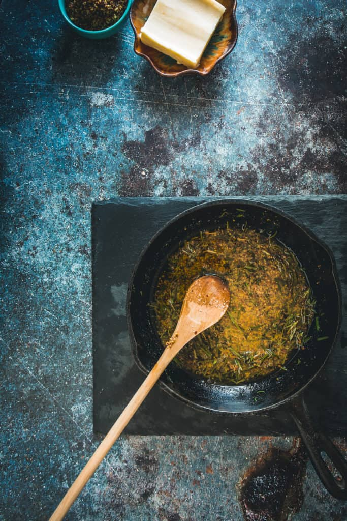 Herbs in melted butter cooking in cast iron pan with wooden spoon