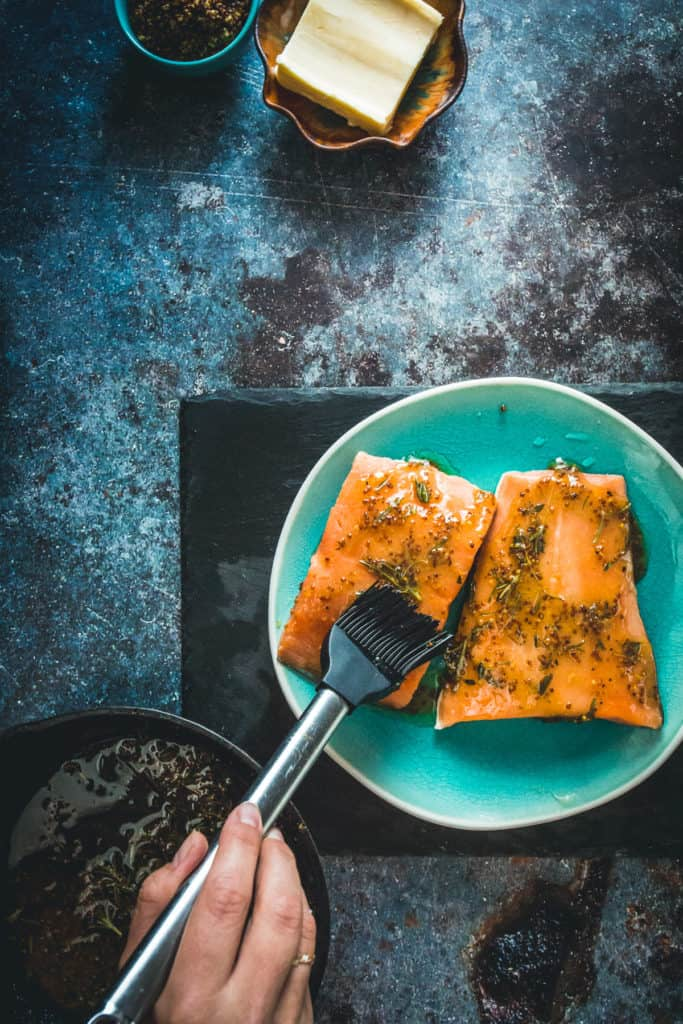 Sockeye salmon being brushed with butter and herbs