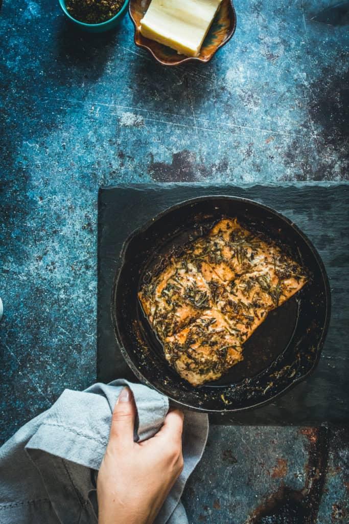 Hand holding pan-fried Sockeye salmon recipe with mustard, honey and wild herbs-18