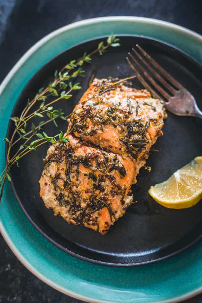 Close up on pan-fried Sockeye salmon recipe with mustard, honey and wild herbs on plate with lemon and fork