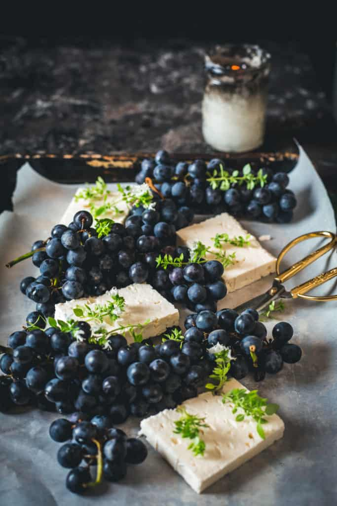 Tray with fresh feta and grapes, scissors and candle