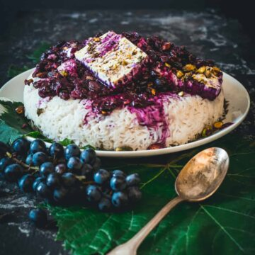 Rice topped with cooked grape sauce and pistachios and feta, spoon in front