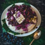Rice topped with cooked grape sauce and pistachios and feta, spoon aside