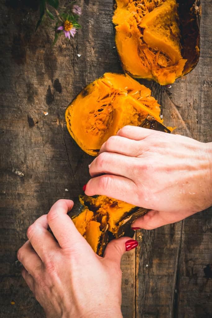 hands ripping pumpkin