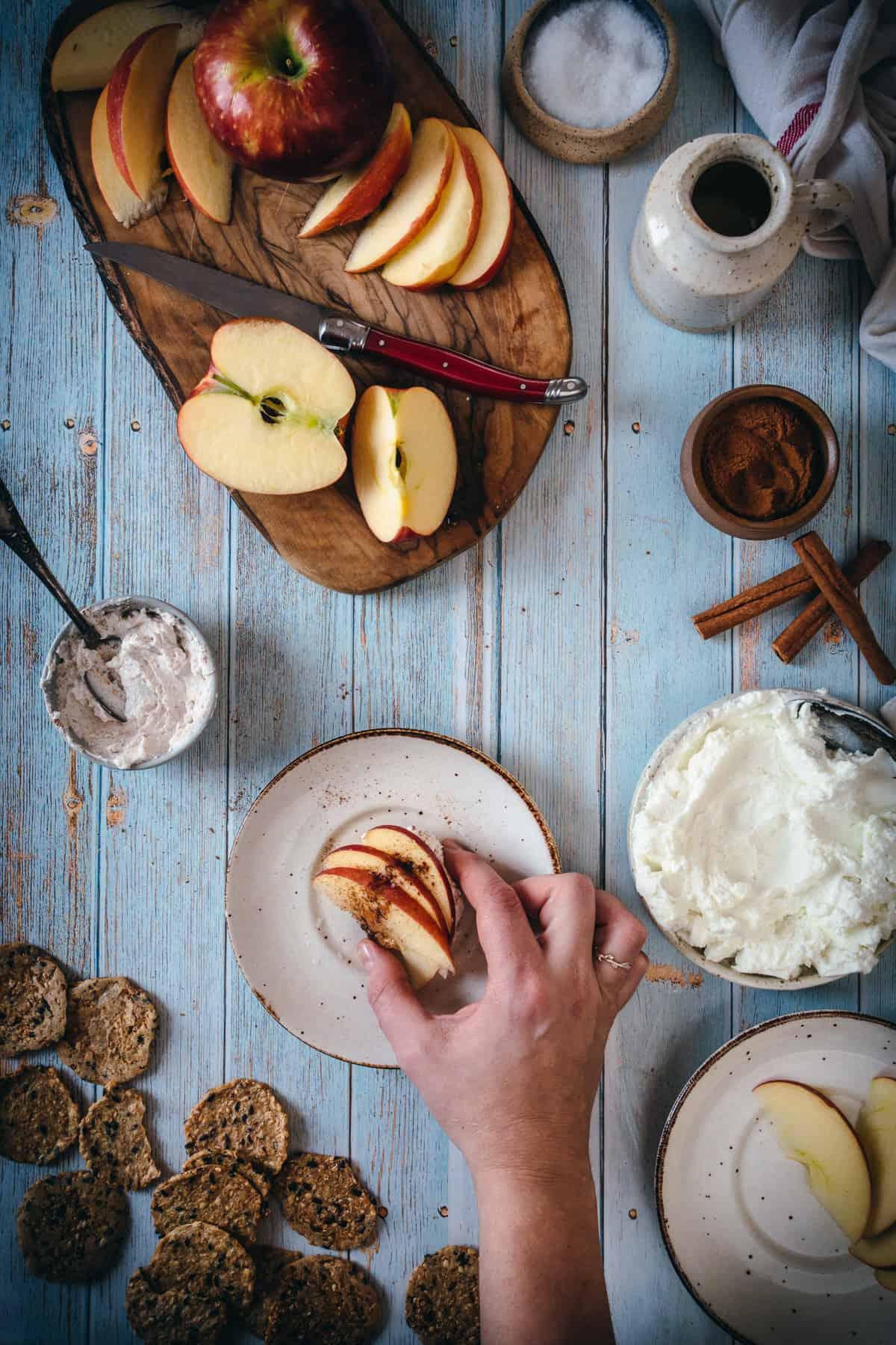 hand grabbing apple labaneh cracker
