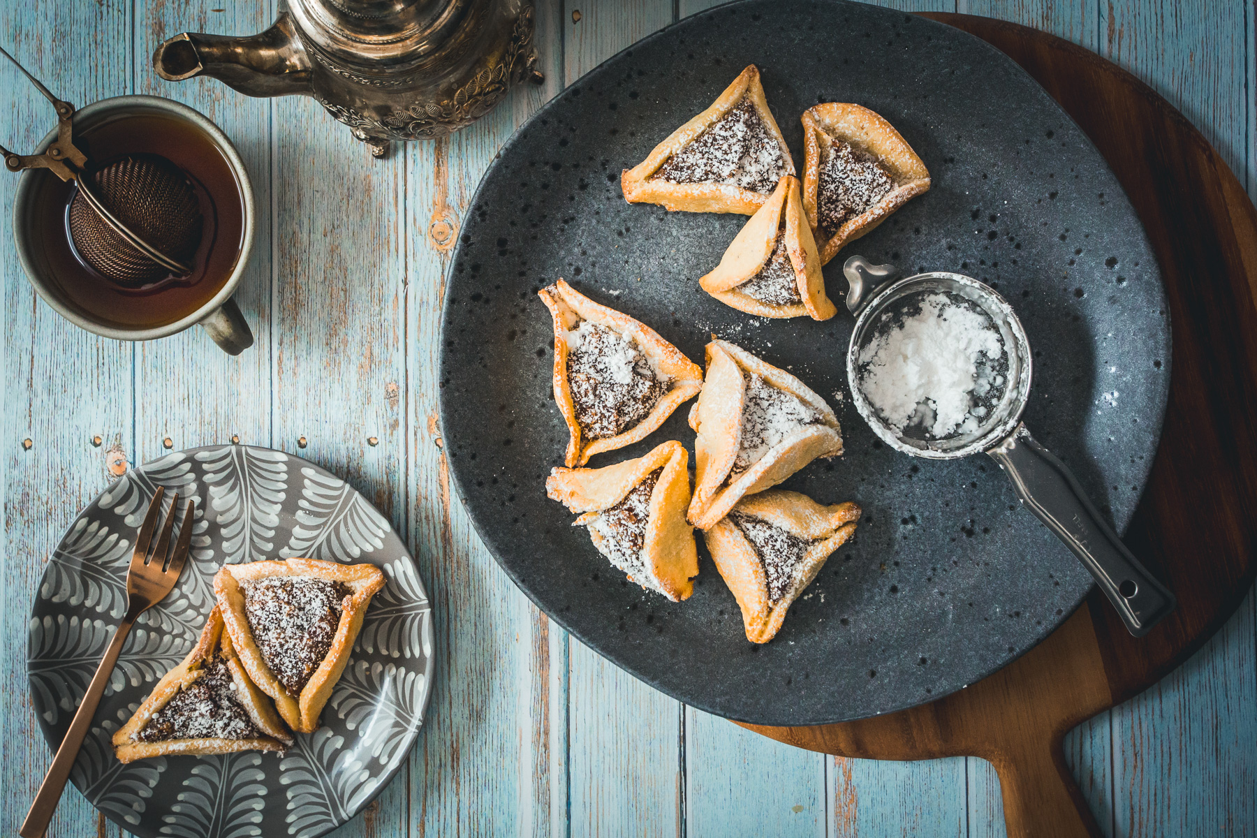 plate of hamantaschen and teapot