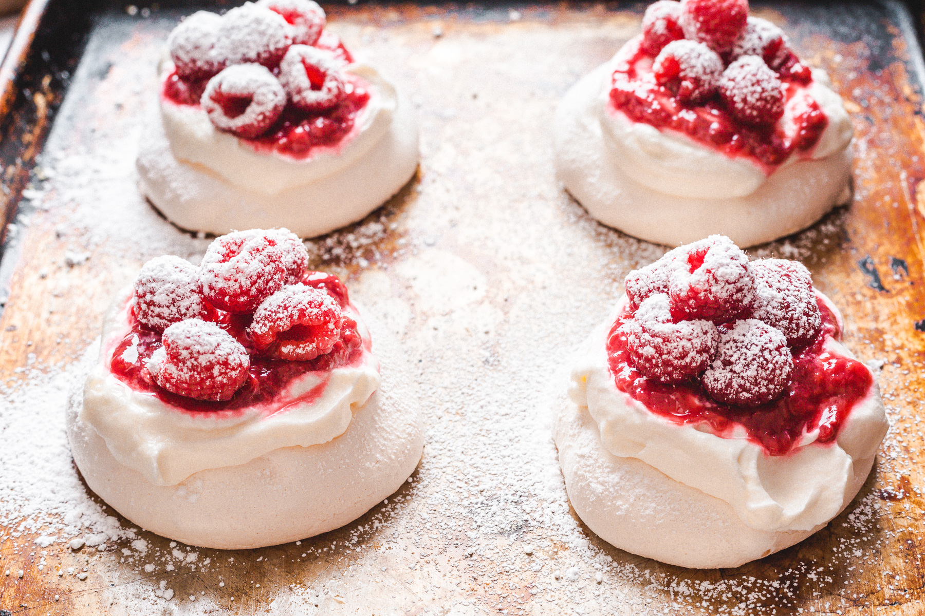 assembled mini pavlovas on baking sheet