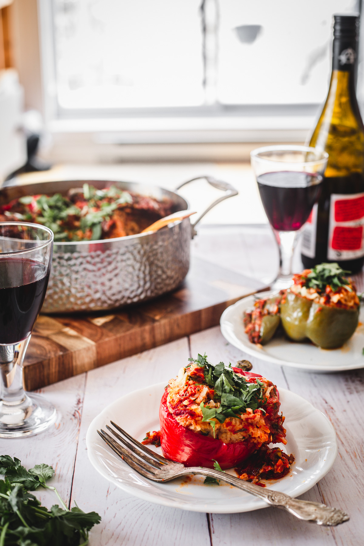 two stuffed peppers, wine glasses, wine bottle and pot with peppers
