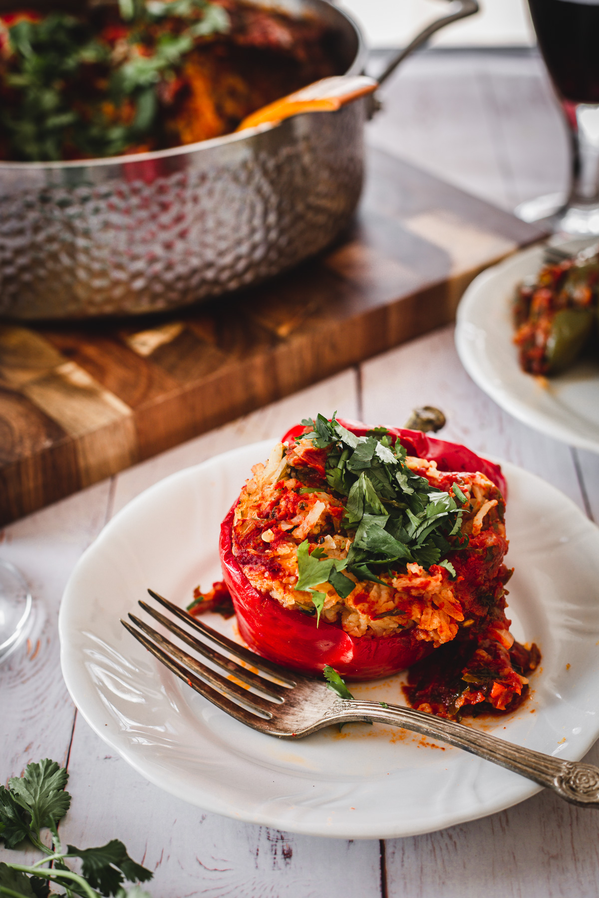 red stuffed pepper, wine glass and fork