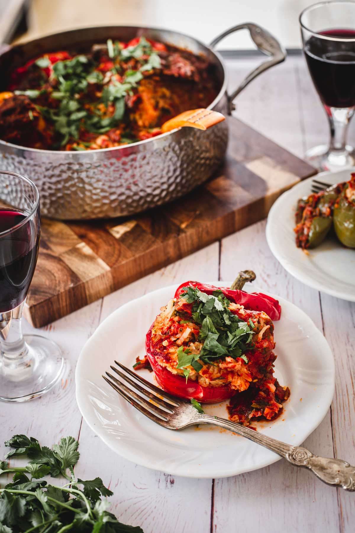 red stuffed pepper, wine glasses, pot with peppers and fork