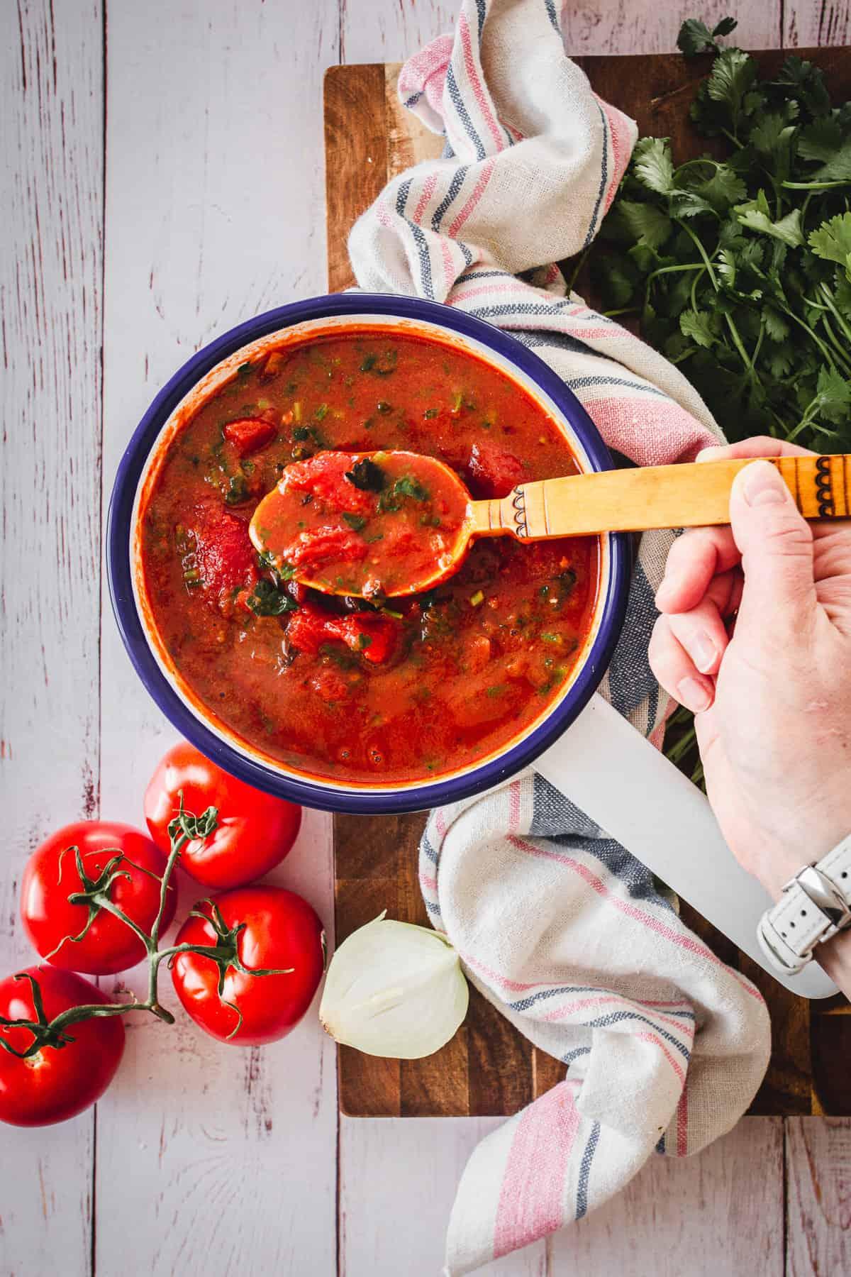 hand mixing tomato sauce