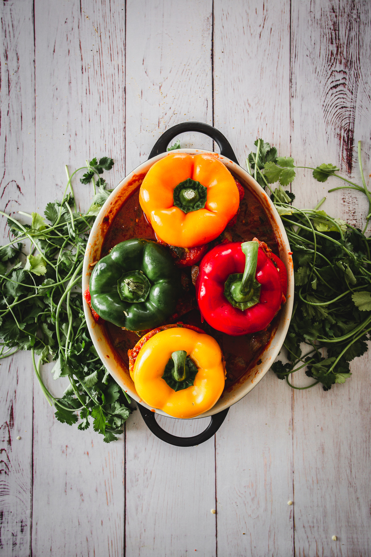 four stuffed peppers in casserole dish