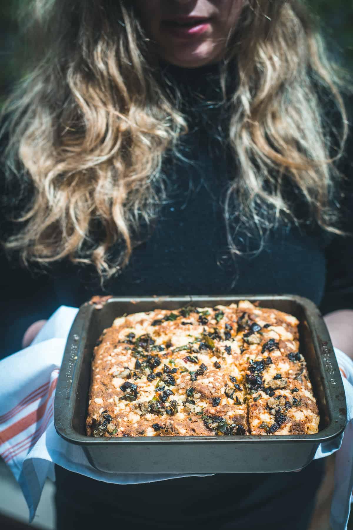 жена, която държи тава с царевичен хляб без глутен