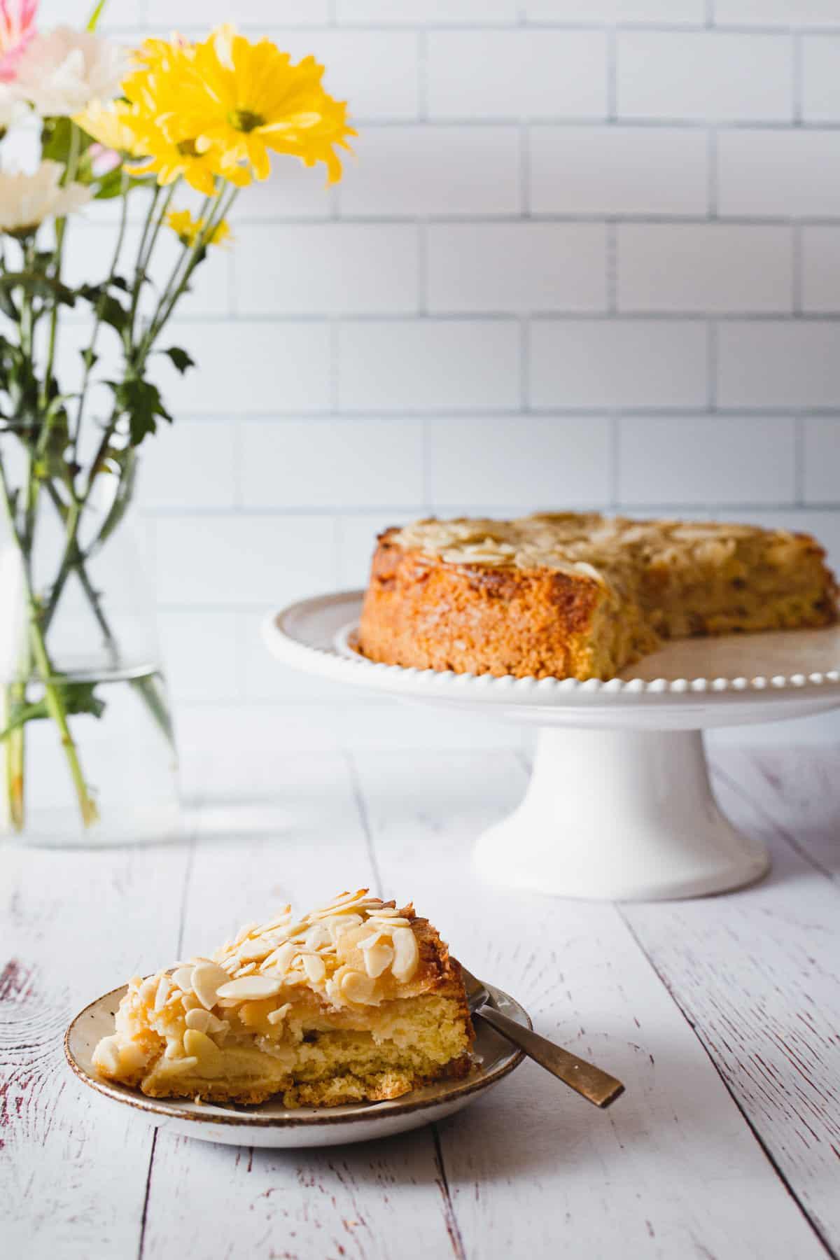 apple cake slice against apple cake in background
