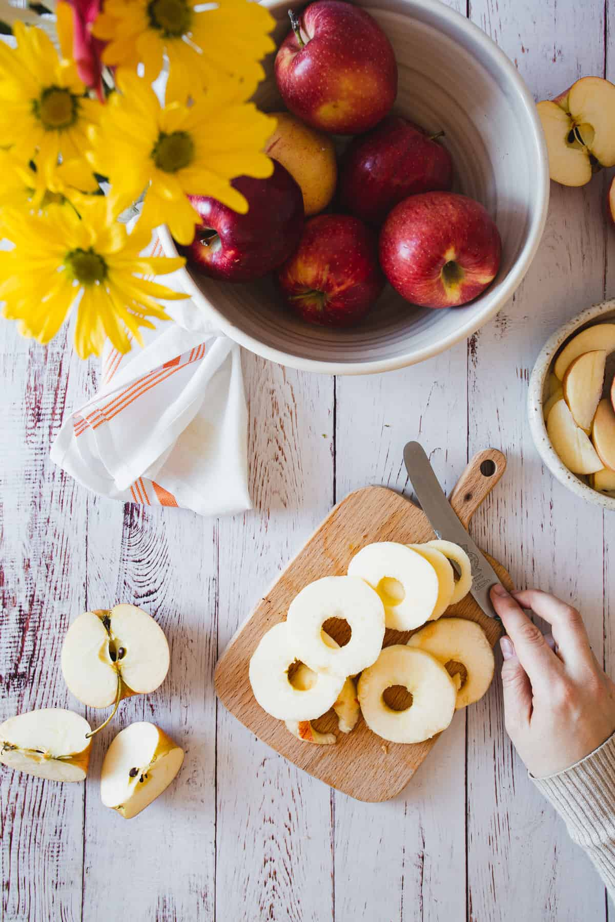 sliced apples on a cutting board with knife