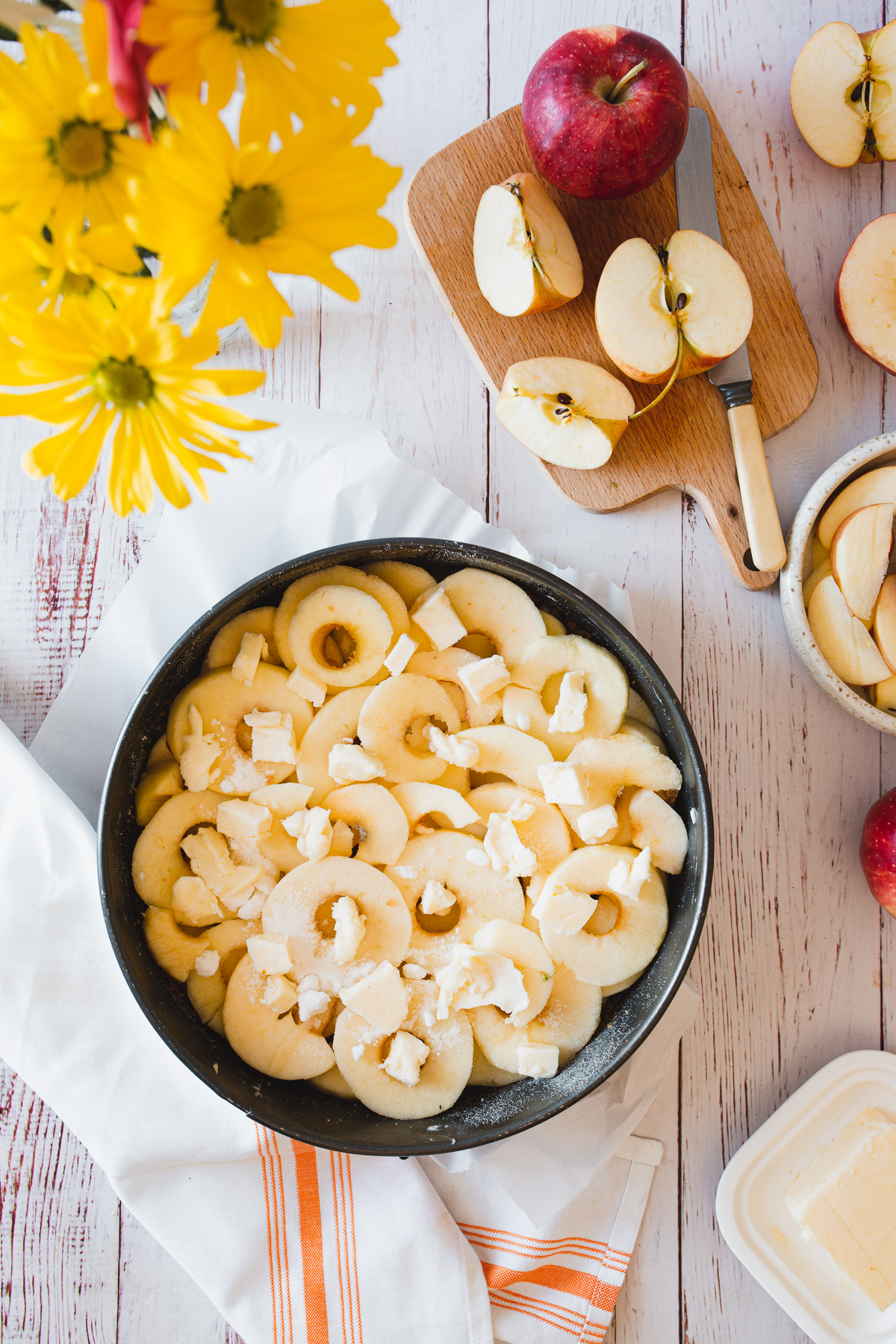 apples in cake pan with butter dotting