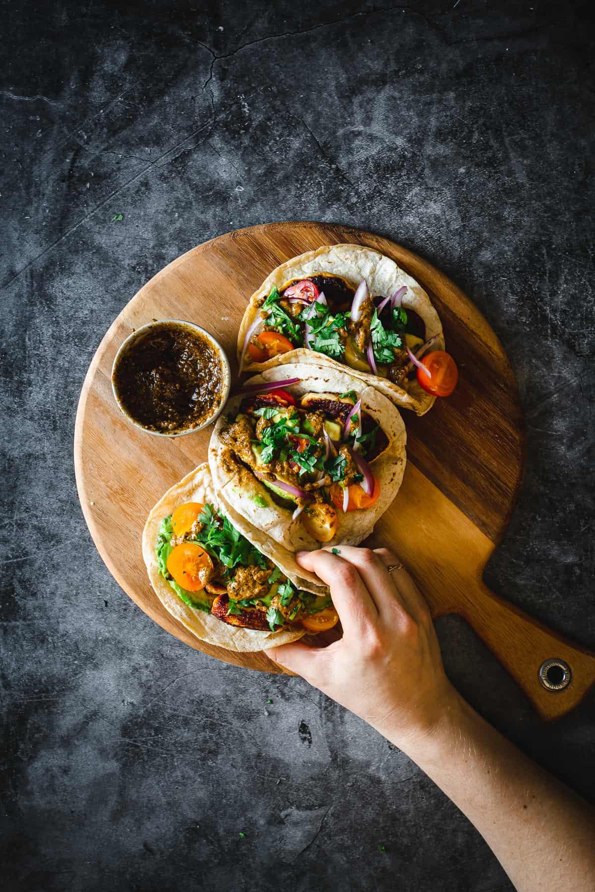 hand grabbing halloumi tacos