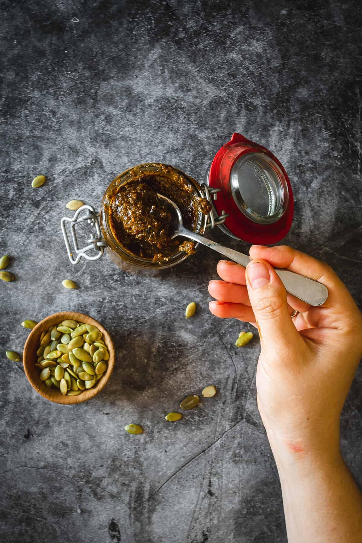 lifting a spoon from a jar of pepita salsa