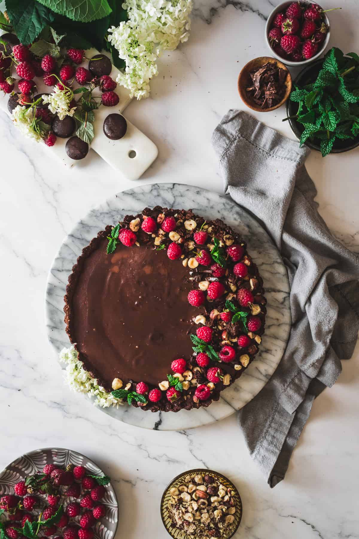 low carb chocolate raspberry tart with little bowls of toppings