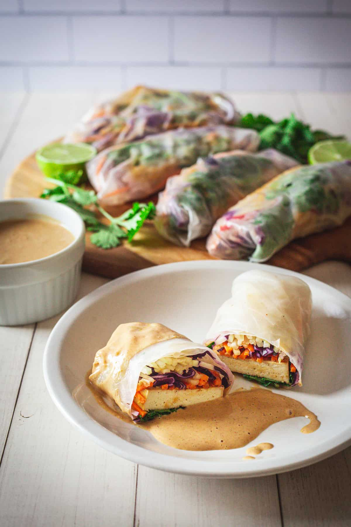 a spring roll on a plate with tofu spring rolls on platter and dipping sauce