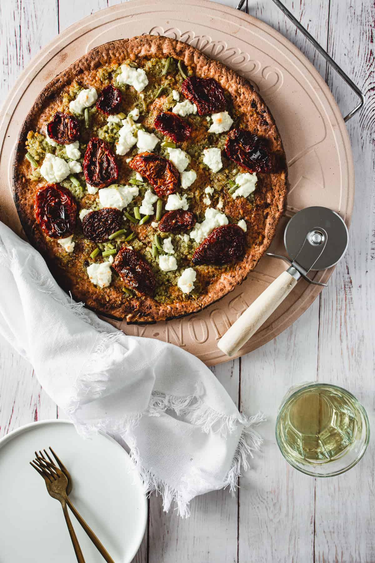 Garlic scape pesto pizza on table