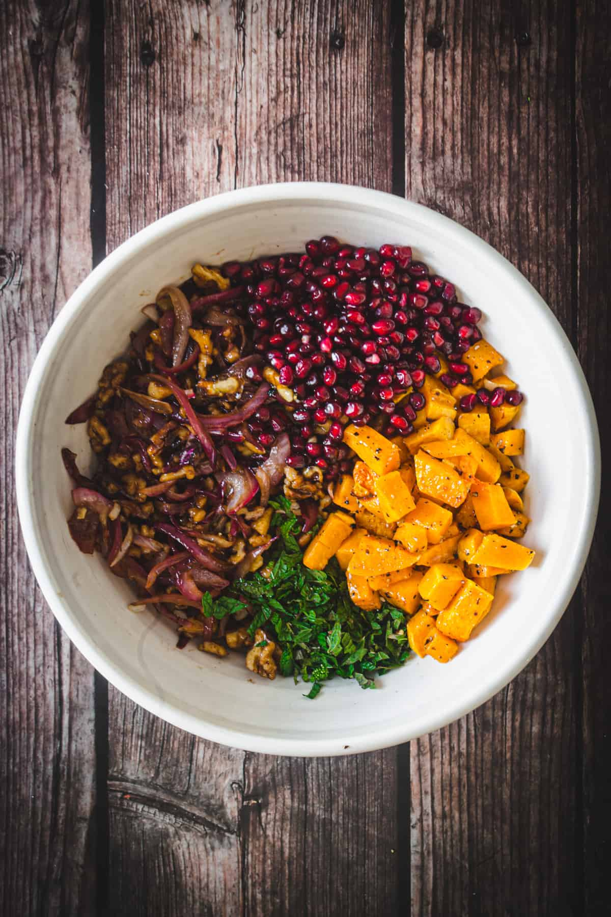 butternut squash, pomegranate, roasted onions and mint in a bowl